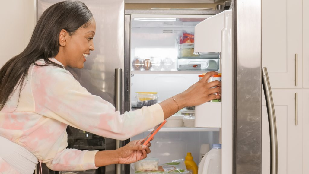 Woman scanning food in her fridge with her phone